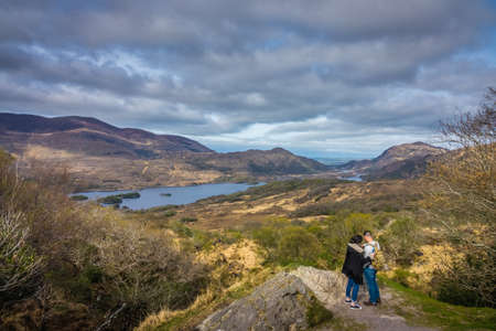 Killarney National Park, Ireland -  April 2017 : Couple of tourists standing on a large rock and taking pictures of the mountains and lakes in the Killarney National Park, Ireland