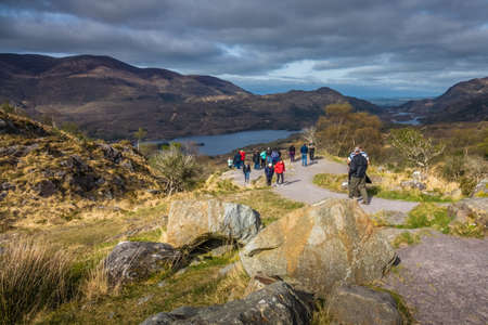 Killarney National Park, Ireland -  April 2017 : Group of tourists walking on the scenic path in the Killarney National Park, Ireland