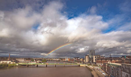 Limerick, Ireland -  April 2017 : Half of a rainbow over river Shannon, hotels and commercial buildings in Limerick town, Ireland Editorial