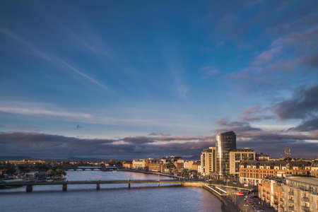 Limerick, Ireland -  April 2017 : Sunset over river Shannon, hotels and commercial buildings in Limerick town, Ireland