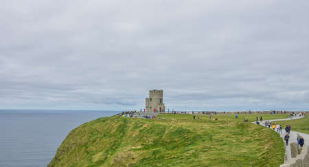 sightseers: Cliffs of Moher, Ireland -  April 2017 : Tourists at the O Briens Tower at the Cliffs of Moher, Ireland