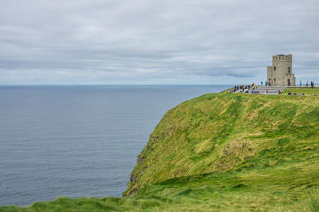 Cliffs of Moher, Ireland -  April 2017 : Tourists at the O Briens Tower at the Cliffs of Moher, Ireland