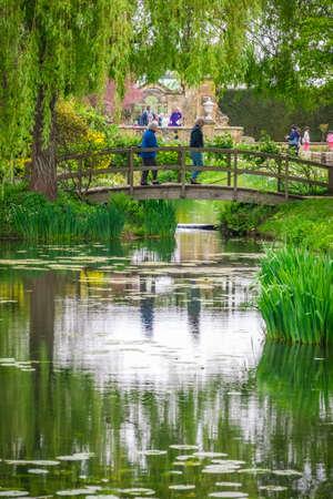 Hever Castle, England -  April 2017 : Elderly people walking over small wooden bridge in the Hever castle gardens, Kent, England, UK
