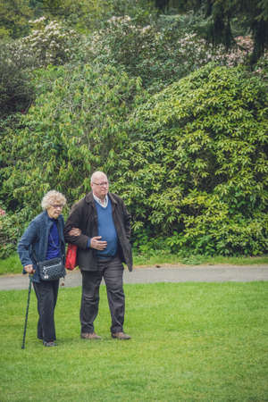 Hever Castle, England -  April 2017 : Middle aged caucasian man walking in the garden with his old mother
