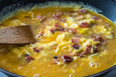 Cooking scrambled eggs with ham and bacon Stock Photo