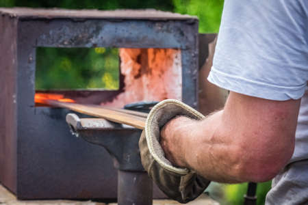 medieval blacksmith: A blacksmith inserting steel rods into the hot oven  during medieval fair festival in Streatham Park in London Stock Photo