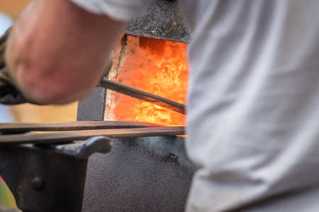 A blacksmith inserting steel rods into the hot oven  during medieval fair festival in Streatham Park in London Stock Photo