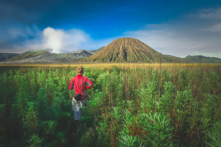 Female tourist walking through the high grass towards the craters of Gunung Bromo and Sumeru volcanoes in Java, Indonesia Stock Photo