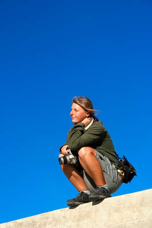 Woman with her DSLR camera on top of a wall waiting for a good photo opportunity Stock Photo