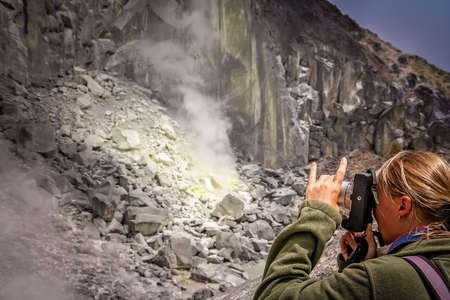 Female trekker and photographer taking images of evaporating sulphur from the crater of the Gunung Sibayak volcano in Sumatra, Indonesia