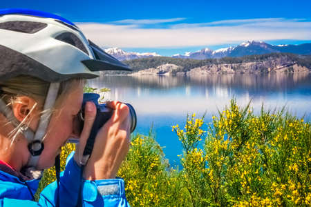 Female cyclists taking pictures  of the stunning landscape of the beautiful lakes in Lake District near Bariloche, Argentina