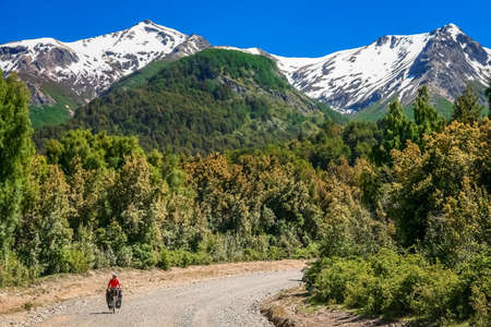 Woman cycling on the corrugated road through the mountains in Lake District, Argentina