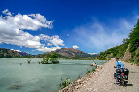 Woman cyclist taking a break during touring trip in Patagonia, Argentina Stock Photo
