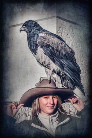 Female tourists with a native to the Andes eagle sitting calmly on her hat in the Colca Canyon in Peru, South America