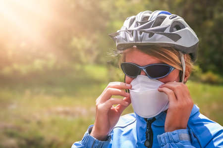Female cyclist wearing a protective face mask preventing from breathing in volcanic dust ash after eruption in southern Patagonia, Chile