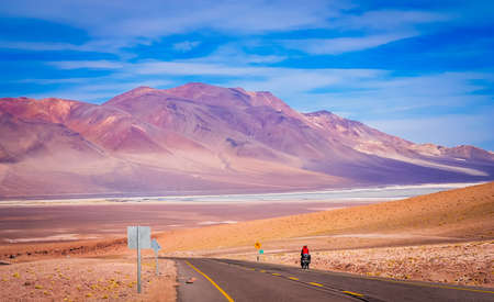 Woman cycling on the paved road from Chile towards Altiplano in Bolivia