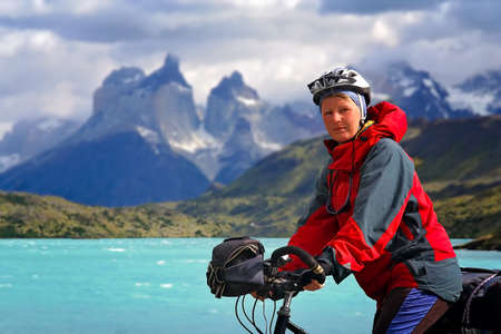 road bike: Girl standing with her bicycle on the road leading to the impressive Cuernos del Paine peaks in Torres del Paine National Park, Chile, South America