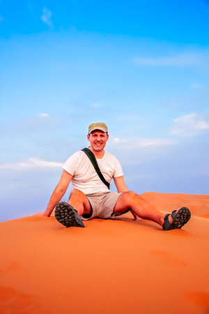 Tourist resting on top of the stunning sand dunes of Sahara desert in Merzouga, Morocco Stock Photo