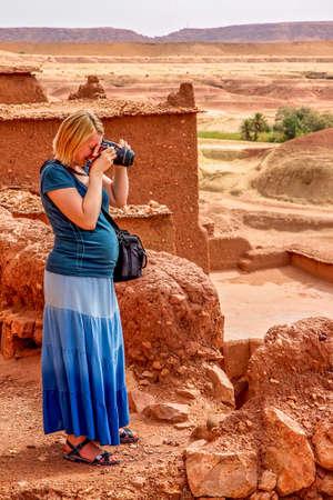 Pregnant woman taking photos inside  Ait Benhaddou, an ancient fortress city in Morocco near Ouarzazate on the edge of the sahara desert.