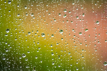 Raindrops on the home window surface against colorful green and yellow background Stock Photo