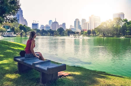public housing: Caucasian female tourist seating on a concrete bench in a public park in Bangkok, Thailand Stock Photo