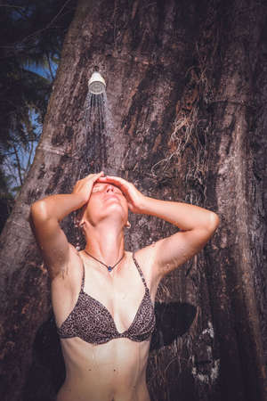 Attractive Caucasian woman taking a shower under a tree on a tropical beach in Thailand photo