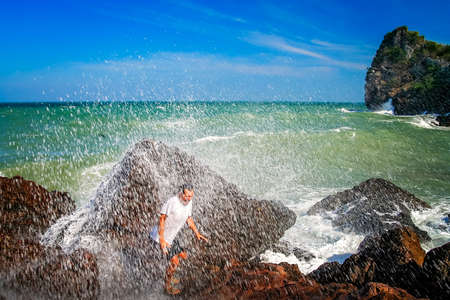 Man escaping incoming big wave on the coast in Thailand Stock Photo