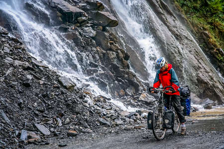 Female passing one of many waterfalls while cycling through the Tiger Leaping gorge, Yunnan Province, China photo