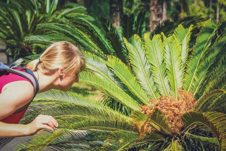 Female tourists taking closer look at one of many tropical plants in botanical garden in Yunnan in China photo