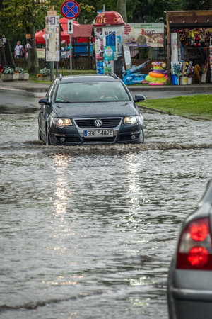 Sarbinowo, Poland -  August 2017 : Car going through the flooded street after extremely heavy rainfall