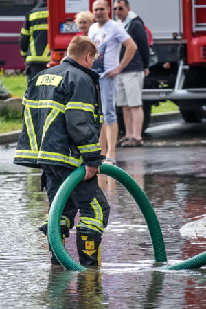 Sarbinowo, Poland - August 2017 : Firefighters pumping out excess water from flooded road after heavy torrential rain