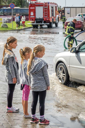 Sarbinowo, Poland -  August 2017 : Three little girls looking at an aftermath of torrential rain Editorial
