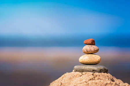 Zen balanced small pile of stacked stones on the beach in summer Imagens