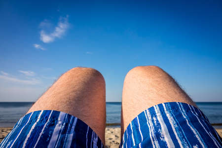 Close up of a legs of a man wearing blue shorts and lying on the beach in summer Stock Photo