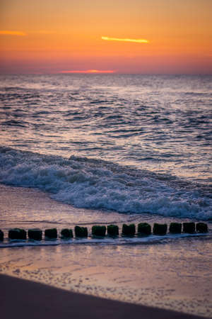 Old wooden breakwaters on the Baltic coast beach photographed at sunset Stok Fotoğraf