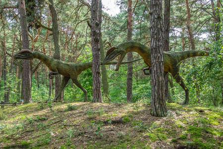 Solec Kujawski, Polen - augustus 2017: twee levensgrote Dilophosaurus-dinosaurussenstandbeelden in een bos