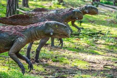 pre: Solec Kujawski, Poland -  August 2017 :  Life sized Raptor dinosaurs statues in a forest