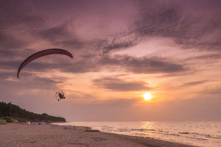 Sarbinowo, Poland -  August 2017 : Paraglider flying with a paramotor over the beach at  sunset