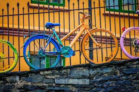 Old rusty vintage bicycle, painted in various colors,  leaning against a railing in Bergen, Norway