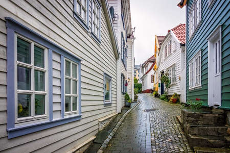 Narrow cobble stoned streets between traditional old colorful houses in the old part of Bergen town, Norway