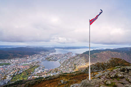 Norwegian flag fluttering on a wind on a pole on top of Mount Ulriken, Bergen, Norway Stock Photo