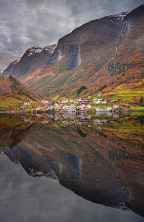 Small homes on the shore of a fjord photographed from a Fjords sightseeing cruise boat in autumn, Norway Stockfoto