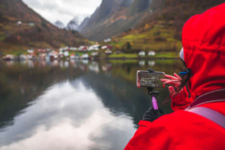 Tourist taking pictures on a smartphone of beautiful fjords during Norway in a nutshell sightseeing cruise through the magnificent Aurlandsfjord and the narrow Nærøyfjord 写真素材