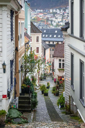 Bergen, Norway -  October 2017 :  Narrow cobble stoned streets between traditional old colorful houses in the old part of Bergen town, Norway