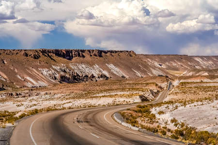 Empty paved road towards Oruro city going through remote part of central Bolivia Stock Photo