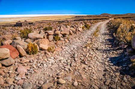 Remote road leading to the biggest of salt lakes, Salar de Uyuni in Bolivia