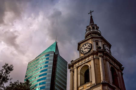 Old church clock tower and modern highrise apartment in Santiago, Chile, South America