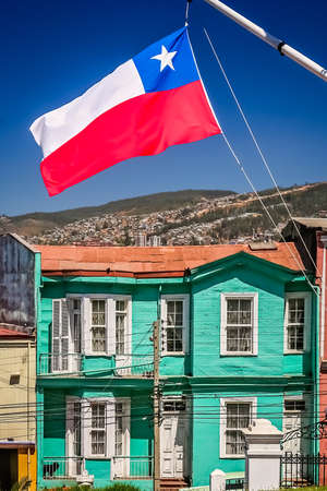 Red, white and blue chilean flag fluttering on a mast in front of the traditional old wooden building on the hilly street in Valparaiso, Chile, South America Stock Photo