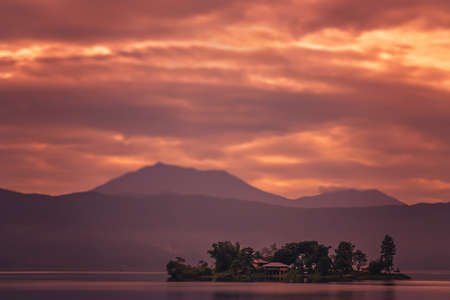 Small home on the tiny island in the middle of the stunning Lake Maninjao at sunset, Sumatra Island, Indonesia Stock Photo