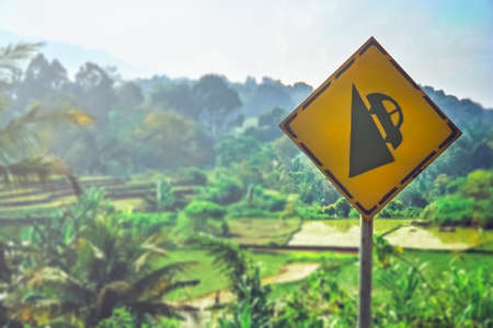 Yellow road sign warning of steep gradient of roads in Sumatran rural countryside, Indonesia Stock Photo